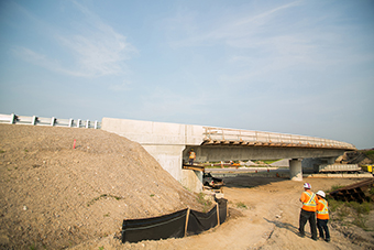 Photo of a bridge under construction with workers on site